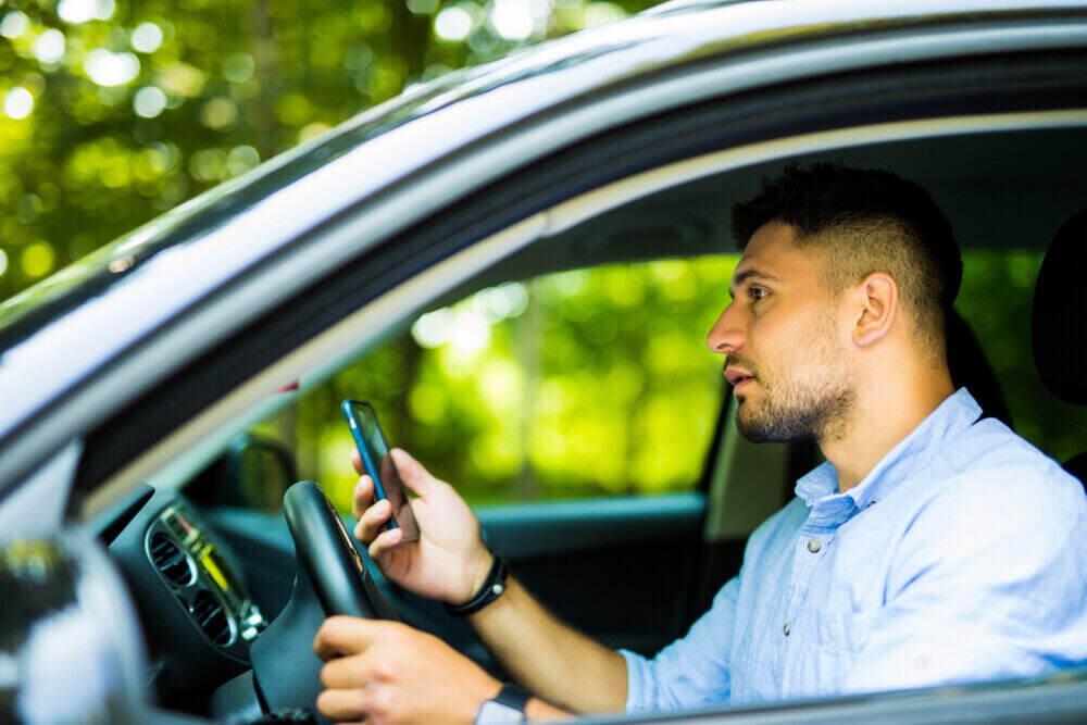 Man driving and looking at his phone