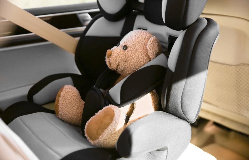 child car seat on a car with a teddy bear
