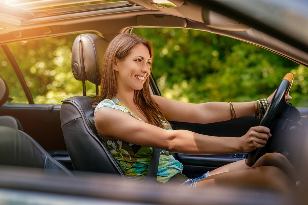 Young beautiful smiling girl driving a car.
